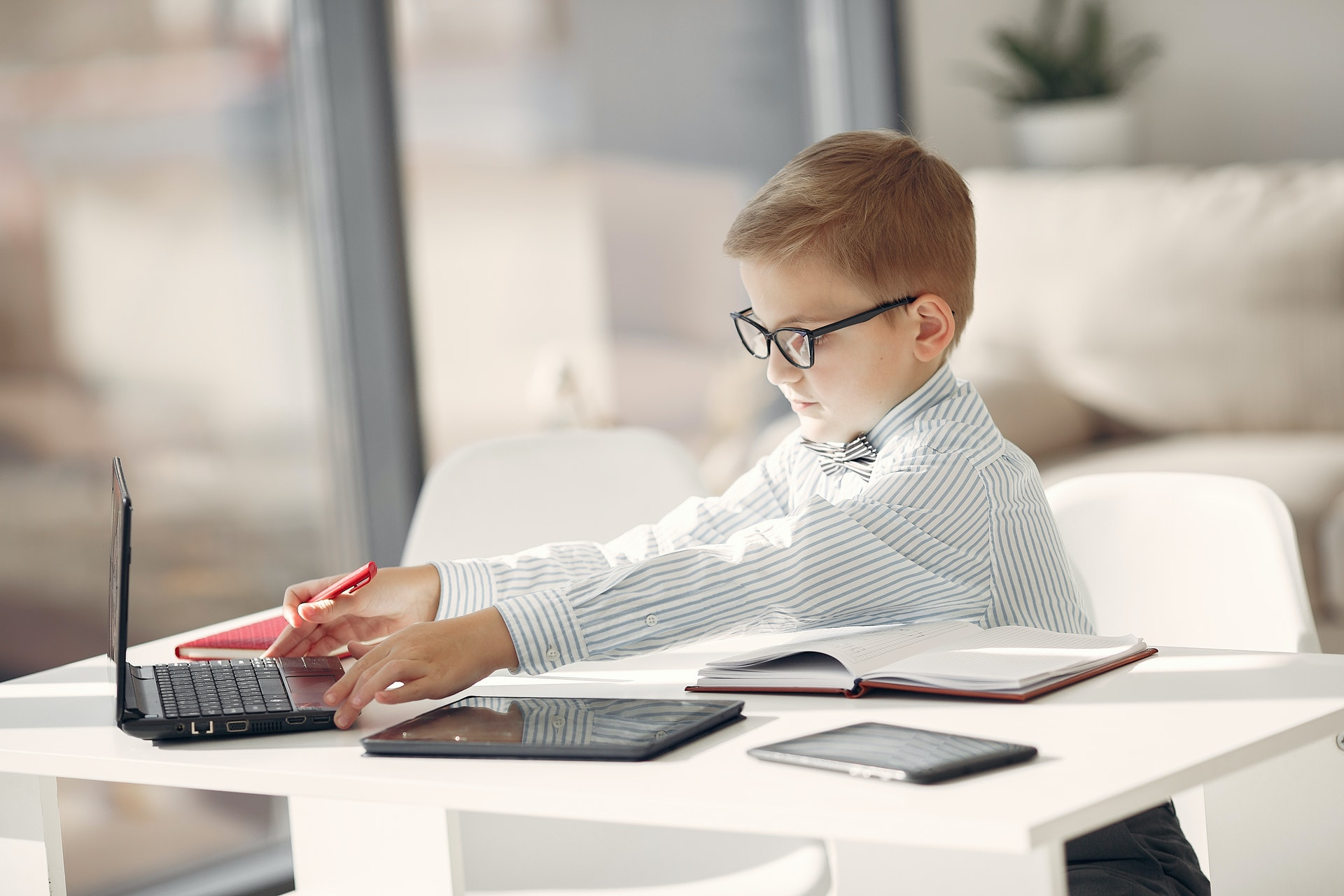 focused-little-businessman-with-laptop-and-other-gadgets-in-3874389